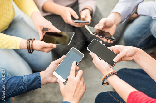 Friends having fun together with smartphones.
