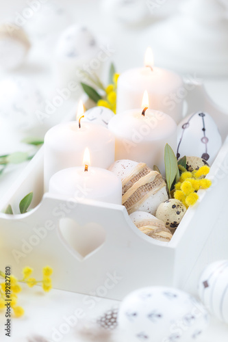 Beautiful Easter composition with white lit candles in a white wooden box with decorated Easter eggs, olive branches and yellow mimosa flowers as a symbol of spring