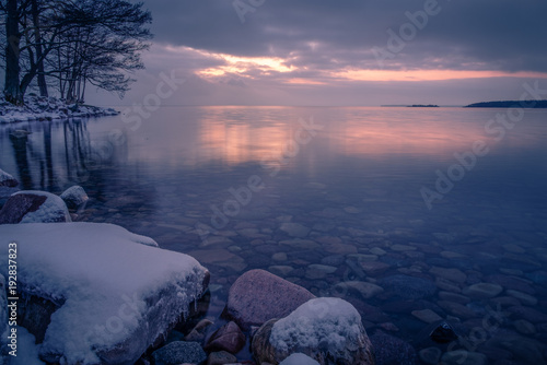 Foto op Aluminium Zee zonsondergang Beautiful sunset with rock and snow in the foreground and sea in the background