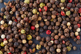 Mix of grind black pepper and black, white, red and yellow peppercorn. Selective focus. - 192840210