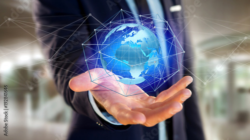 Foto Murales Businessman holding a Connected network over a earth globe concept on a futuristic interface - 3d rendering