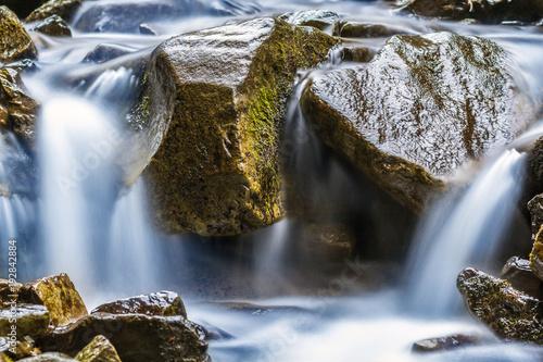 Mały wodospad z niebieską spienioną wodą na mokrych kamieniach