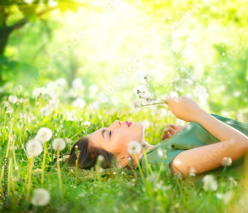 Leinwanddruck Bild Beautiful young woman lying on green grass and blowing dandelions. Allergy free concept