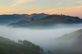Beautiful mountain landscape of a foggy morning with a colorful sky and trees, Dumesti, Romania - 192848207