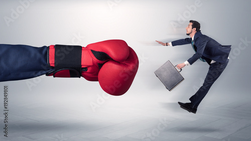 Giant hand gives a kick to a small businessman - 192849801