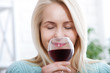 Closeup portrait of female customer drinking red wine with eyes closed.