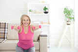 Deep squat. Front view of middle aged woman in sportswear doing squat and holding dumbbells while standing in front of window at home.