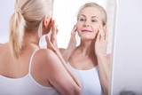 Middle aged woman looking at wrinkles in mirror. Plastic surgery and collagen injections. Makeup. Macro face. Selective focus - 192853097