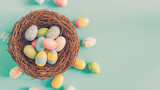 Colorful easter egg and nest on green pastel color background with space.