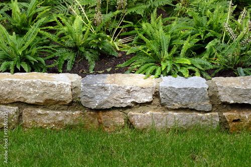 Foto op Plexiglas Baksteen muur Kleine Mauer aus Natursteinen als Abgrenzung zum Pflanzbeet