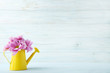 Watering can with pink flowers on wooden table