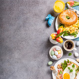 Easter breakfast flat lay with scrambled eggs bagels, orange tulips, bread toast with fried egg and green asparagus, colored quail eggs and spring holidays decorations. Top view. Copy space. - 192873445