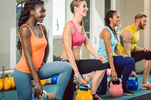 Foto Murales Gruppe von Männern und Frauen bei Fitness Training mit Kettlebell