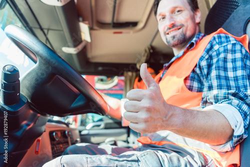 Fototapeta Fernfahrer Mann sitzt in seinem LKW und zeigt den Daumen hoch