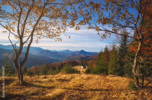 Fotobehang Herfst Lonely house on a meadow in a mountain valley