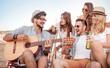 Beautiful young people with guitar having fun on beach.