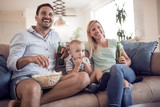 Happy family watching TV on sofa at home. - 192893091