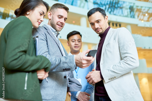 Low angle portrait of modern businessman holding smartphone showing something to group of colleagues standing in hall of office building