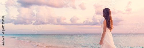 Leinwanddruck Bild Peaceful vacation paradise woman walking on sunset beach with pastel colors sky and ocean for tranquility and serenity banner. Girl in white wedding dress relaxing on luxury tropical summer getaway.