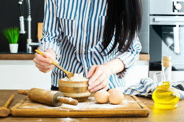 Female hands making dough on kitchen background