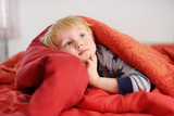 Cute little boy in pajamas having fun in bed after sleeping and watching TV or dreaming - 192908487