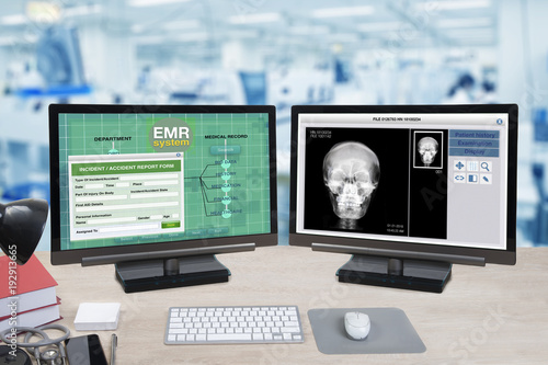 Foto Murales Health information and patient x-ray show on two computer monitors on doctor desk.