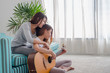 two girl friends playing guitar at sofa in living room near window at home with happniess moment.lesbian lifestyle.love wins.