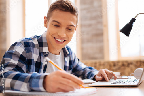 My favourite subject. Handsome smiling fair-haired boy working on his laptop and writing in his notebook while sitting at the table
