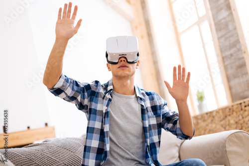 Virtual reality. Concentrated well-built stylish adolescent wearing a VR headset and relaxing while sitting on the sofa