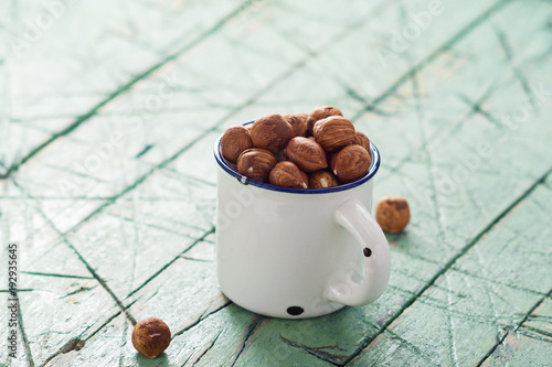 Hazelnuts in white cup on old wooden table. copy space.