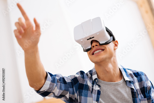 Entertainment. Joyful well-built stylish adolescent wearing a VR headset and relaxing and touching the imaginary picture