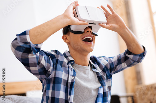 Having great time. Cheerful stylish well-built adolescent smiling wearing a VR headset and touching it