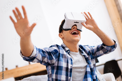 My favourite activity. Happy well-built stylish adolescent smiling wearing a VR headset and touching the imaginary picture