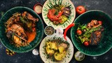 A set of dishes of meat and fresh vegetables and fish on a wooden table. Top view. Free space for your text.