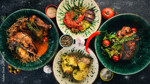 Wall mural A set of dishes of meat and fresh vegetables and fish on a wooden table. Top view. Free space for your text.