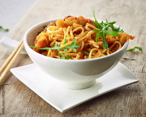 Wall mural Bowl of asian noodles with fried meat