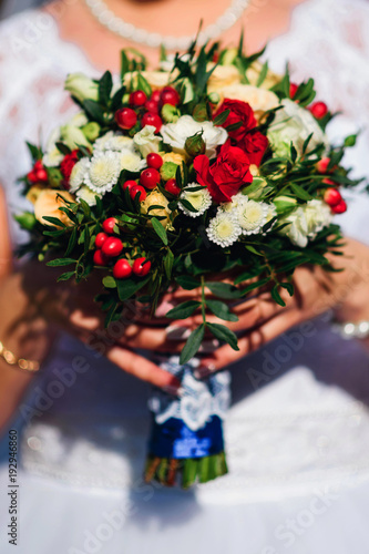 wedding bouquet with red roses and white daisies in hands of the bride on the background of dress