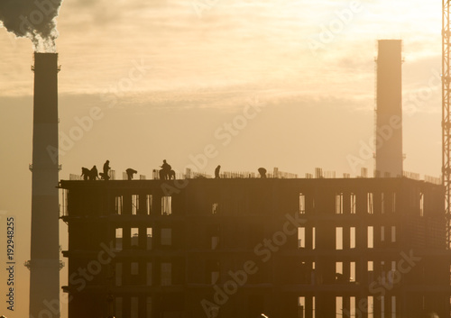 Construction side - silhouette at sunset - workers, cranes - unfinished building