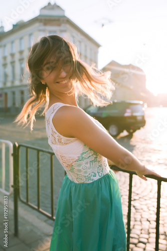 Tender blonde woman with charming smile posing at the sunrise and sun glare