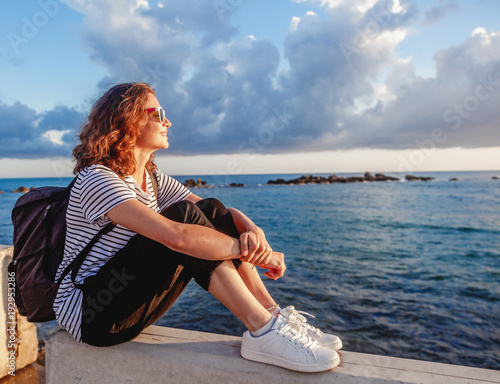 portrait of a beautiful happy young woman sitting on the background of the sea and a beautiful sunset and admiring the scenery