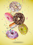 Tasty doughnuts in motion falling on pastel yellow background. - 192957012