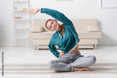 smiling-girl-sitting-in-lotus-position-on-yoga-mat-and-stretching-at-home