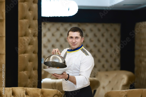 Wall mural chef presenting a dish at the hotel restaurant, steaming a dish with a cover lid