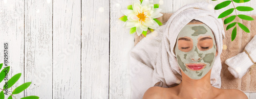 Fototapeta Young healthy woman with face clay mask.