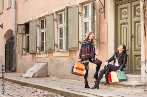 Friends tell jokes and laugh at them. Spending time in old town in autumn day
