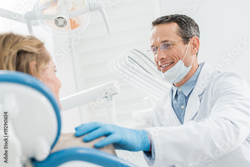 Smiling doctor consulting female patient in modern dental clinic