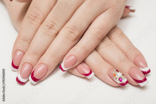 Fototapeta Manicure. White nails with red hearts. Isolated.