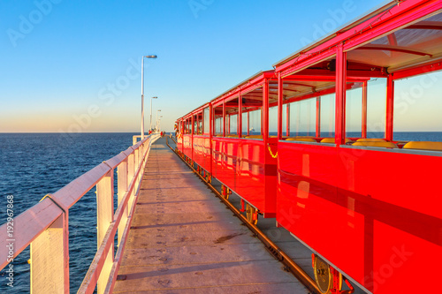 Fotobehang Rood Perspective view of vintage red electric train going on Jetty Busselton tracks in Busselton, Western Australia. Famous place at sunset light. Busselton Jetty is the longest wooden pier in the world.