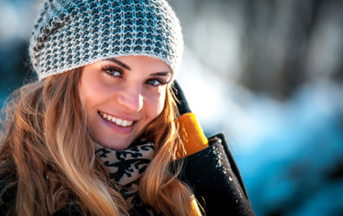 Portrait of smiling woman in the winter park at sunny day
