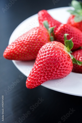 Fresh strawberries on plate on black background